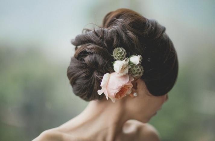 Voluminous textured wedding updo with fresh flowers