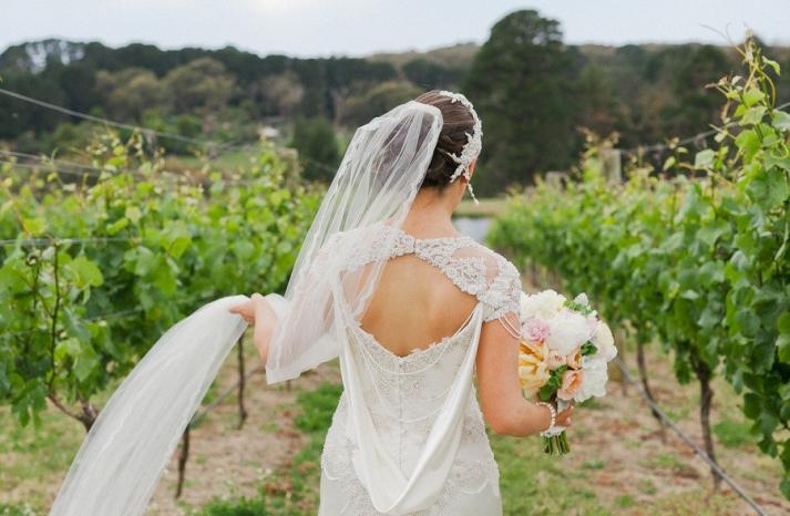 Bohemian bride walks through vineyard in romantic statement back wedding dress