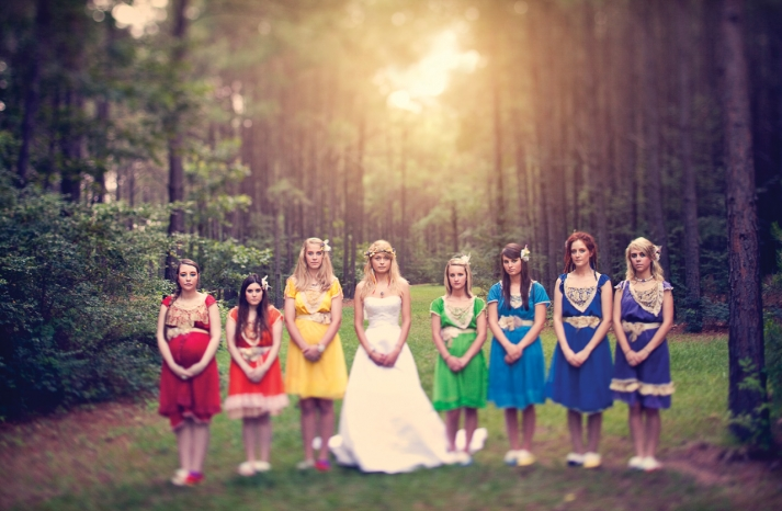 Rainbow bohemian bridesmaids pose outdoors with bride