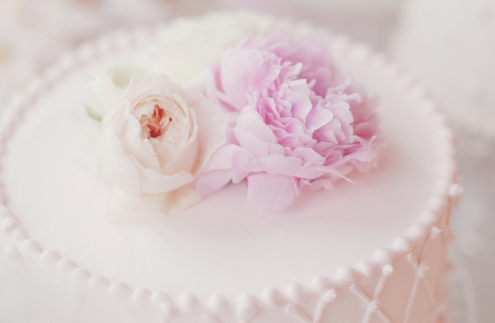 Romantic wedding cake topped with pale pink peonies