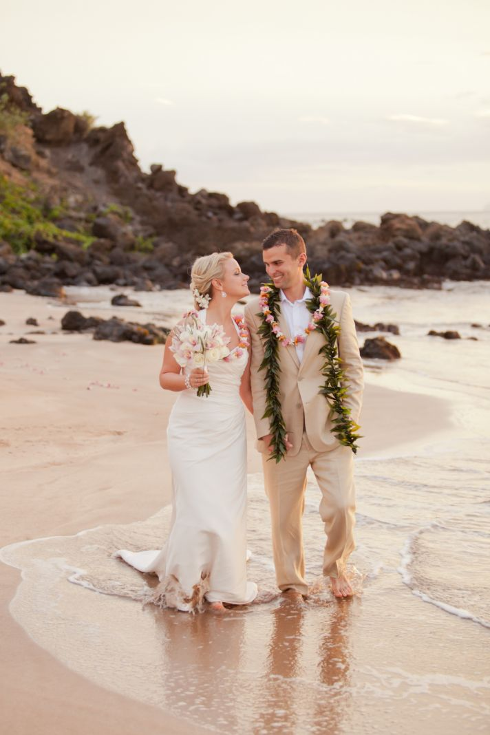 Maui bride and groom walk hand in hand on beach