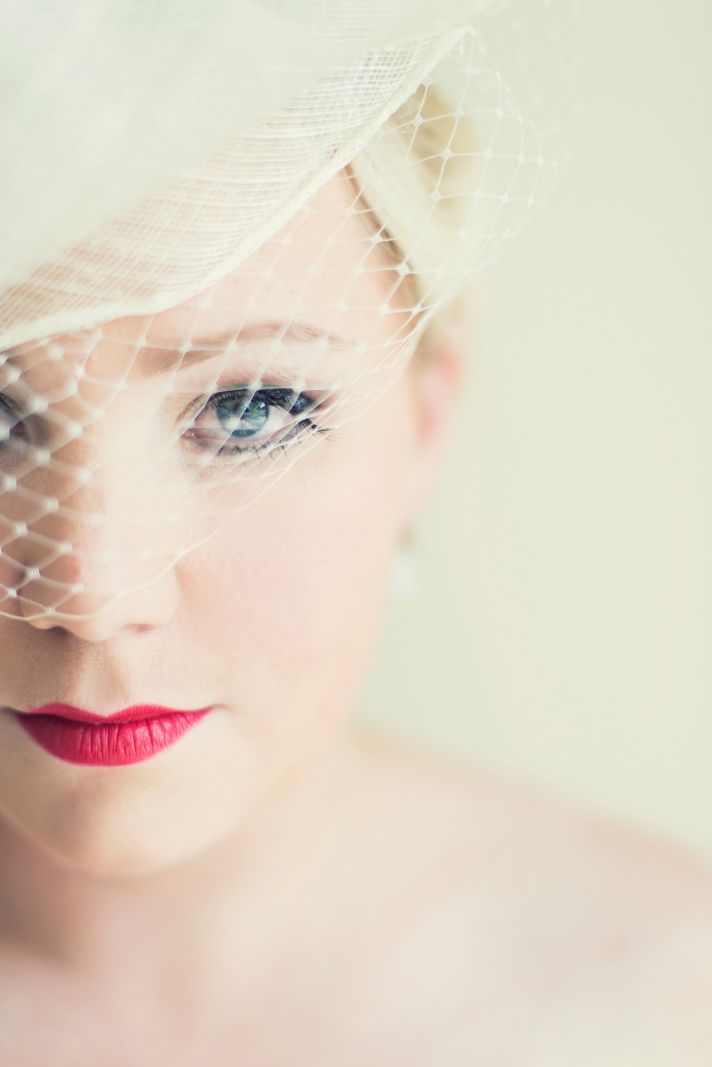 Platinum blonde bride wears birdcage veil deep red lips