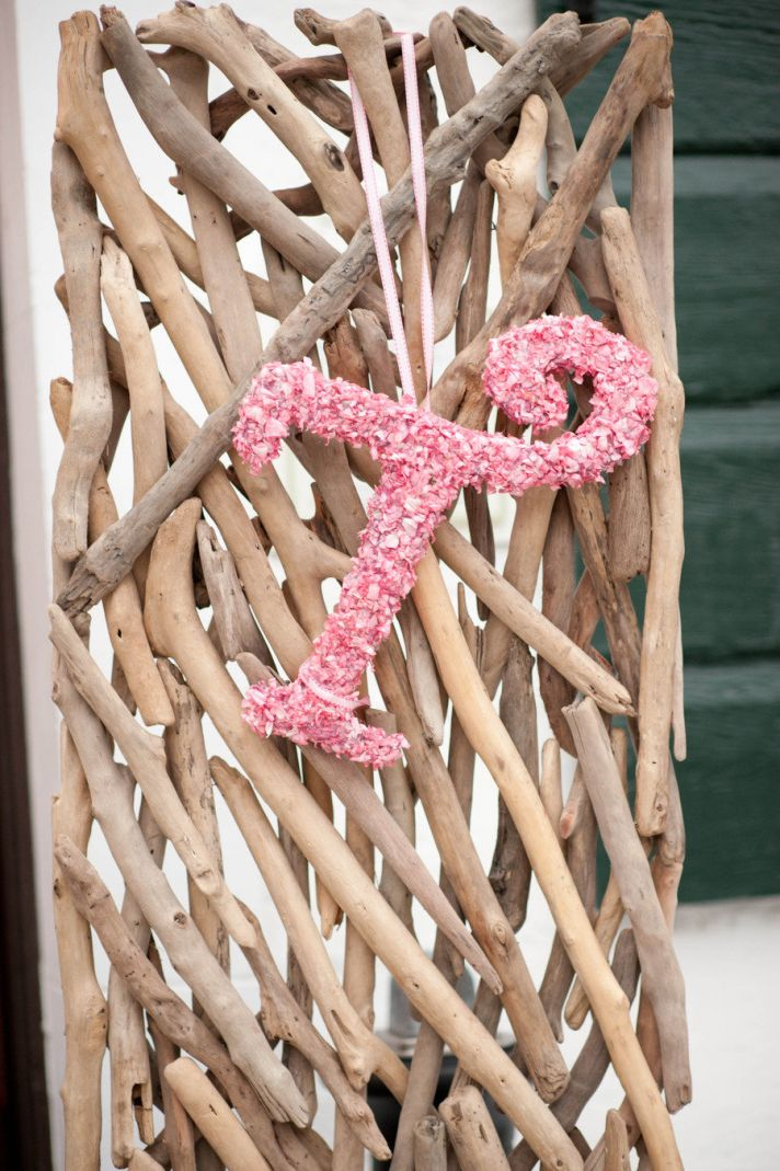 Pale pink wedding flower initials hang from beachwood backdrops