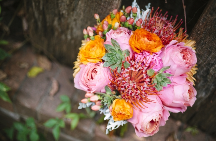 Bright summer wedding whimsical bouquet of roses ranunculus and succulents