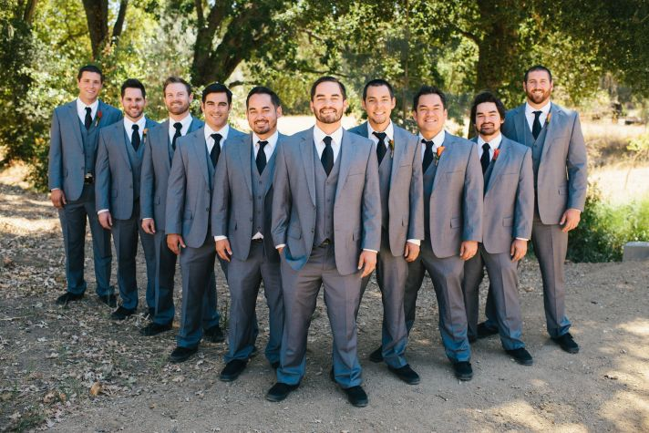 Groom and groomsmen pose outdoors in gray 3 piece suits