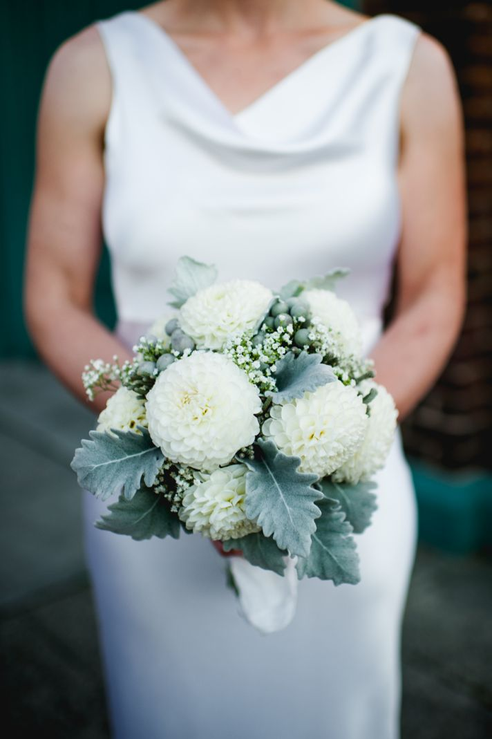 Bride wears simple white silk wedding dress with draped cowl neckline