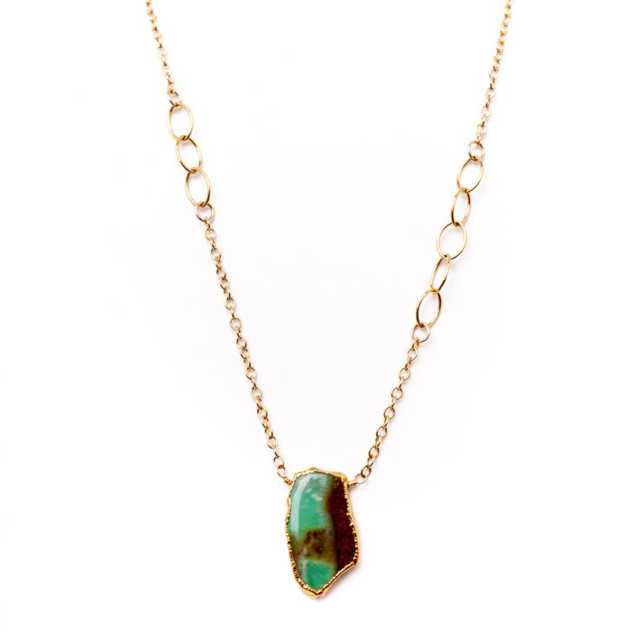Gold necklace with a green gem